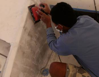 Beng sanding in front of the salon (wall was cut open)