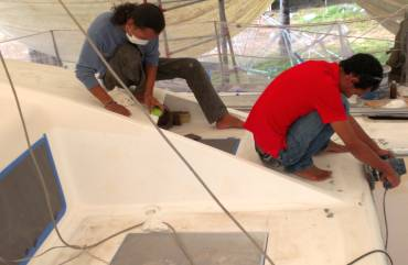 Jack & Baw smoothing Ocelot's foredeck for gelcoat