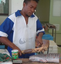 Chopping fish steaks with a machete & a wooden stick