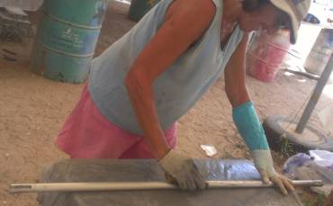 Sue sanding a spreader bar - a latex glove keeps her cast dry