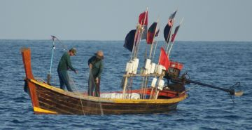 Thai fishermen pull a net. Note flags with floats.
